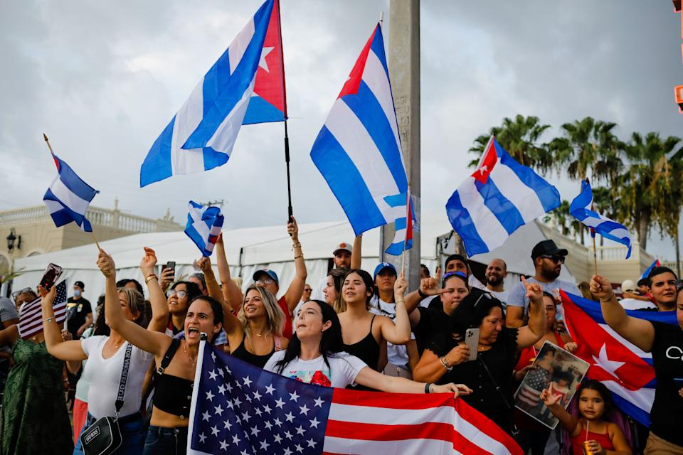 People demonstrate, some holding Cuban and US flags, during a protest against the Cuban government at Versailles Restaurant in Miami, on July 12, 2021.  Havana on Monday blamed a US