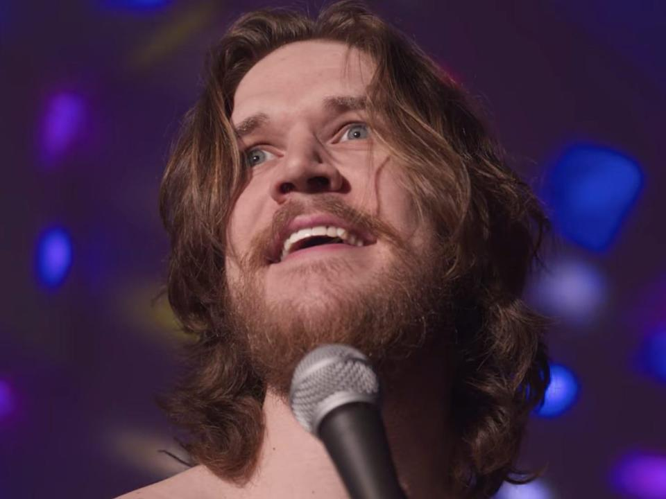 A close up of a man (Bo Burnham) singing into a microphone with dotted lights behind him.