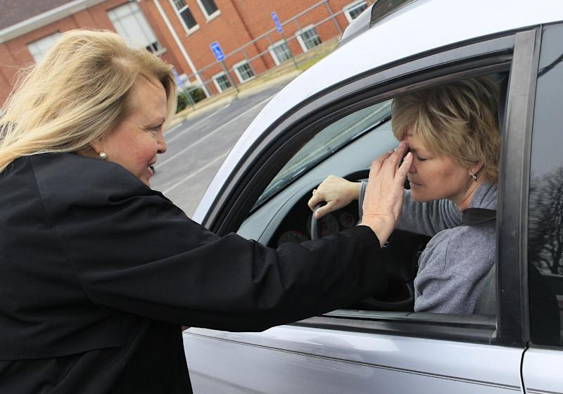 The Rev. Patricia Anderson Cook gives the blessing to Carolyn Grome as she sits inside her car during drive thru Ash Wednesday services at Mt. Healthy United Methodist Church, Wednesday, Feb. 22, 2012, in Mt. Healthy, Ohio. (AP Photo/Al Behrman)