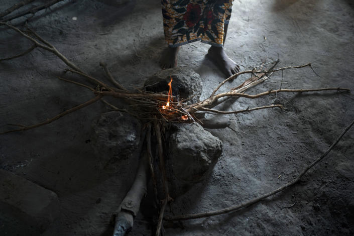 Lama Mballow stands next to the fire before cooking rice in her home in Bansang, Gambia, Wednesday, Sept. 29, 2021. Mballow, who has a 4-year-old son and another child on the way, has no plans to get vaccinated after giving birth. The persistent rumor that COVID-19 vaccines affect fertility has been especially troublesome in predominantly Muslim countries like Gambia and Somalia were polygamy is common. (AP Photo/Leo Correa)