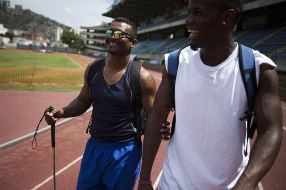 Fernando Ferrer (L), 34, a blind runner member of Venezuela's Paralympics team, and his guide Manuel De La Rosa, smile after a practice session in Caracas April 16, 2012.