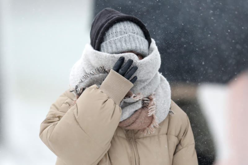 A woman walking the half mile from the Chicago Aquarium to the Adler Planetarium braces in a stiff wind and blowing snow off Lake Michigan, Monday, Nov. 11, 2019, in Chicago. (AP Photo/Charles Rex Arbogast)