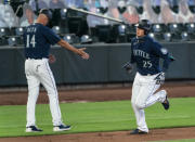 Seattle Mariners' Dylan Moore, right, is congratulated by third base coach Manny Acta after hitting a solo home run off Texas Rangers starting pitcher Kolby Allard during the third inning of a baseball game, Monday, Sept. 7, 2020, in Seattle. (AP Photo/Stephen Brashear)