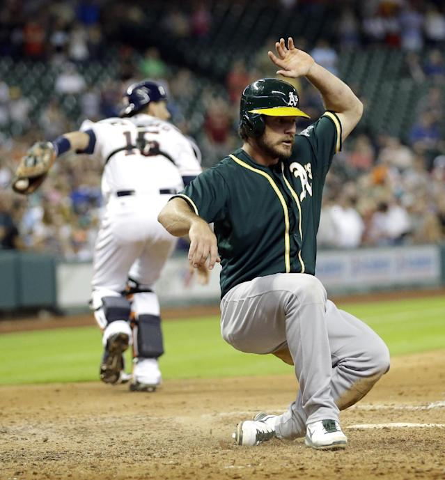Oakland Athletics' John Jaso, right, slides across home plate to score the tying run as Houston Astros catcher Jason Castro (15) handles the throw during the ninth inning of a baseball game Tuesday, July 29, 2014, in Houston. (AP Photo/David J. Phillip)