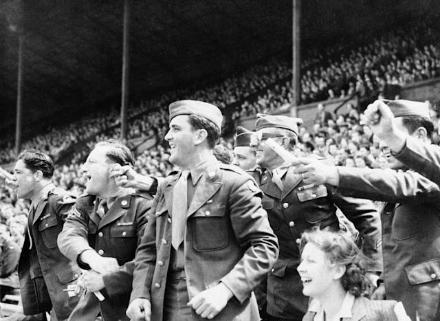 Go east, go west, go up to the fighting fronts - and youíll hear the American cry of ìPlay Ball!î Baseball, the American National Pastime, goes everywhere with our servicemen, and Britain is no exception in London, England June 9, 1944. Wembley Stadium, famed for international soccer play, resounded to American Huzzahs and Bronx cheers as baseball nines of the U.S. Ground Forces and U.S. 9th Air Force --- play brings a group of U.S. soldier to their feet. (AP Photo)