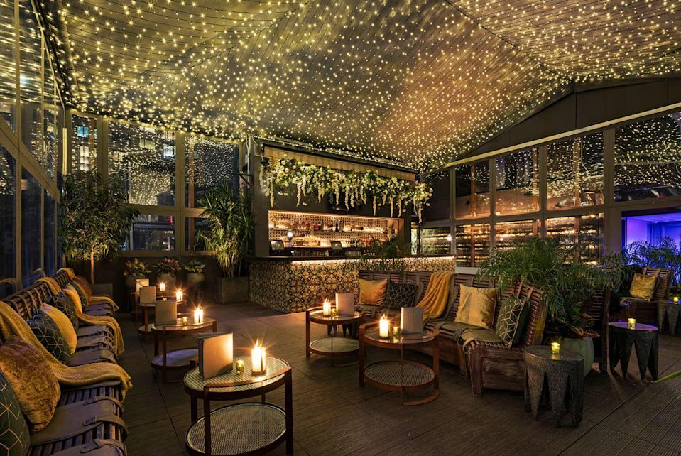 """<p>For a touch of <em>amour</em>, <a href=""""http://www.phdterrace.com/"""" rel=""""nofollow noopener"""" target=""""_blank"""" data-ylk=""""slk:PHD Terrace at Dream Midtown"""" class=""""link rapid-noclick-resp"""">PHD Terrace at Dream Midtown</a>'s enclosed rooftop bar has transformed into a romantic winter garden inspired by Shakespeare's<em> A Midsummer Night's Dream </em>including scores of twinkle lights and lush installations of gold and white florals including a flower-filled walkway that practically begs to be Instagrammed. Seasonal tastes will include an oversized Nutella stuffed cookie that serves 12, an ornament filled with Peppermint Mojito, and a glittering Goldtini.  </p><p><em>210 West 55th Street.</em></p>"""