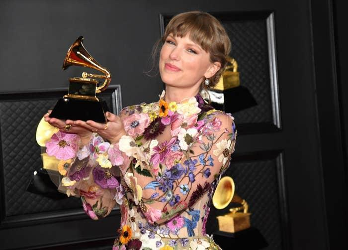 Taylor posing in a floral print gown as she shows off her Grammy