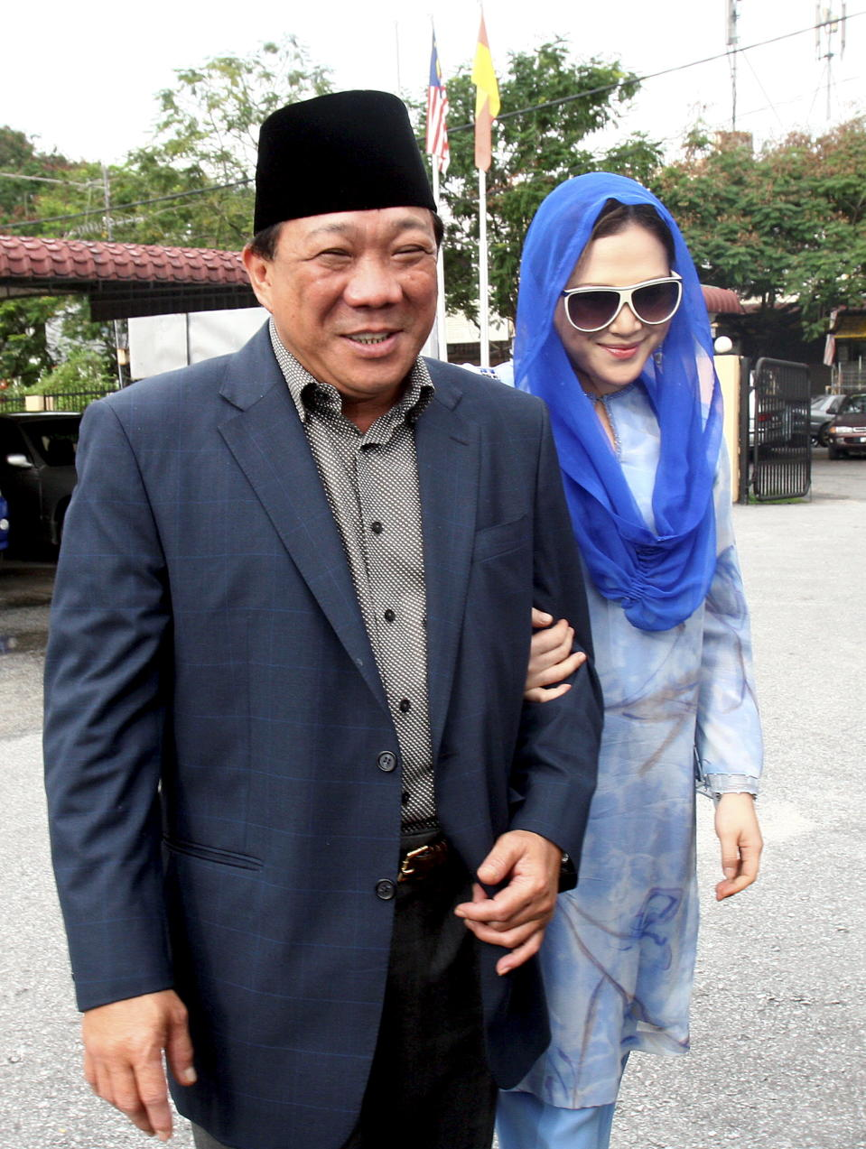 This photo taken on May 19, 2010 shows Malaysian lawmaker Bung Mokhtar Radin (L) and his second wife Zizie Ezette (R) arriving at a Shariah court in Kuala Lumpur. (Photo credit should read AFP/AFP via Getty Images)
