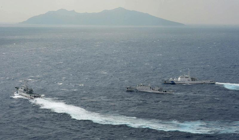 FILE - In this Sept. 24, 2012 file photo, Japan Coast Guard vessels sail along with Chinese surveillance ship Haijian No. 66, center, near disputed islands called Senkaku in Japan and Diaoyu in China, seen in background, in the East China Sea. Chinese patrol boats have harried the Japanese Coast Guard many times a week for more than a month in an unusually relentless response to their latest maritime spat. China says ships from its Marine Surveillance service are merely defending Chinese sovereignty and protesting illegal Japanese control over the uninhabited islands, known as Senkaku in Japan and Diaoyu in China. (AP Photo/Kyodo News, File) JAPAN OUT, MANDATORY CREDIT, NO LICENSING IN CHINA, HONG KONG, JAPAN, SOUTH KOREA AND FRANCE