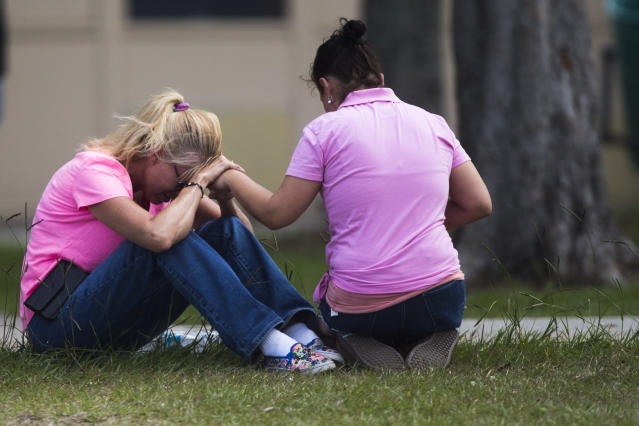 <p>Two women pray outside the family reunification site following a shooting at Santa Fe High School on Friday, May 18, 2018, in Santa Fe, Texas. (Photo: Marie D. De Jesus /Houston Chronicle via AP) </p>