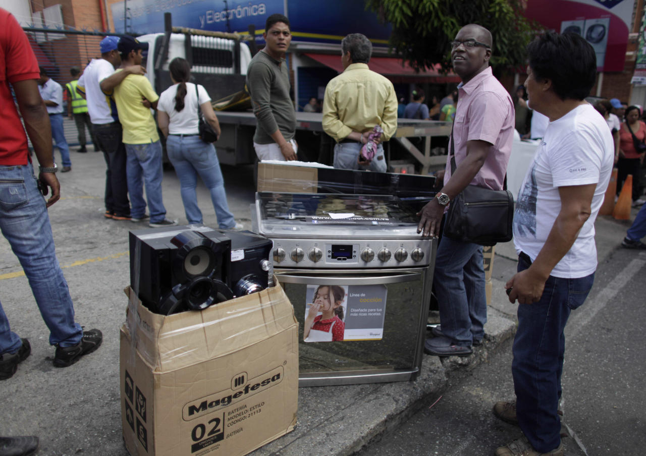 "People stand with their recently purchased goods outside an appliance store in Caracas, Venezuela, Monday, Nov. 11, 2013. President Nicolas Maduro seized control of a nationwide chain of appliance stores Friday seeking to battle inflation and shortages. Shoppers were still arriving Monday to join the hundreds who began amassing over the weekend after price inspectors said they found evidence of ""usury"" and Maduro ordered the chain Tiendas Daka ""occupation."" (AP Photo/Ariana Cubillos)"