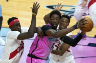 Miami Heat center Bam Adebayo, center, looks to pass as Toronto Raptors forward Pascal Siakam, left, and guard Kyle Lowry defend during the second half of an NBA basketball game, Wednesday, Feb. 24, 2021, in Miami. (AP Photo/Lynne Sladky)