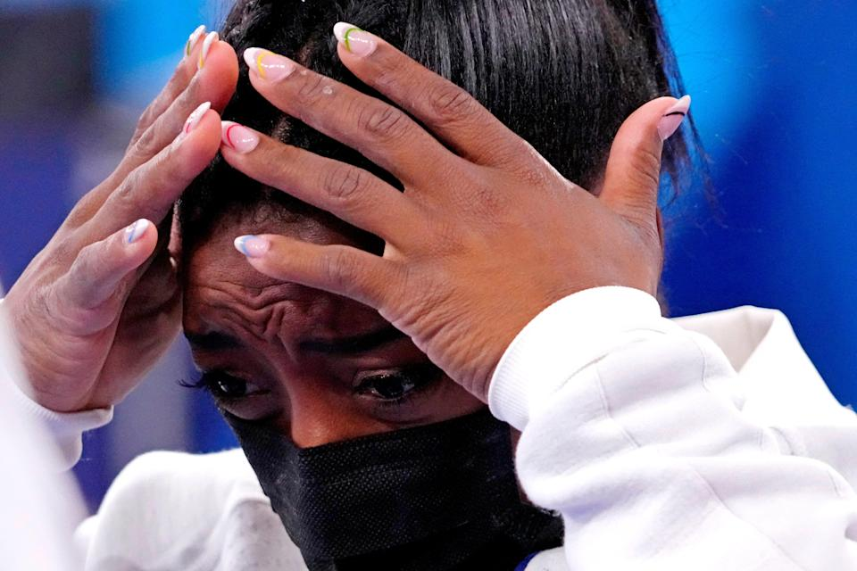 Simone Biles reacts after pulling out of the women's gymnastics team final.