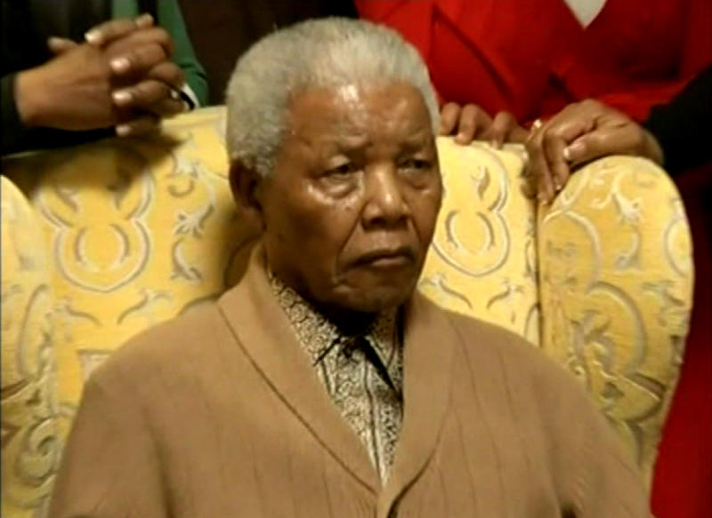 This video image taken from SABC television shows South Africa's former president Nelson Mandela as he receiving a torch to celebrate the African National Congress' centenary from ANC chairperson Baleka Mbete, unseen, in Mandela's home village Qunu in rural eastern South Africa Wednesday May 30, 2012.  Nelson Mandela's African National Congress brought its centenary celebrations to his home village in rural eastern South Africa.  (AP Photo/SABC via AP video)   SOUTH AFRICA OUT
