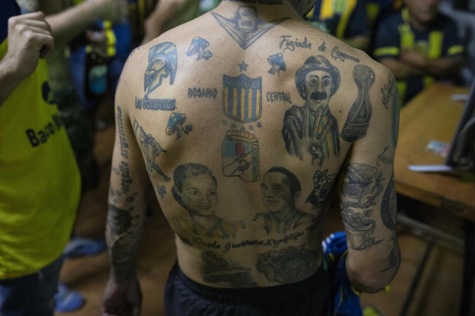 """A Rosario Central soccer fan's back is filled with tattoos, with his team's shield at center, during a gathering by the team's fan club """"Defensores de Tablada"""" to watch the team's match against Newell's Old Boys on television amid COVID-19 restrictions in Rosario, Argentina, Sunday, May 2, 2021. Few places in the world have soccer fans more passionate than those in Argentina, and few have been so long denied a live view of their teams due to the pandemic. (AP Photo/Rodrigo Abd)"""