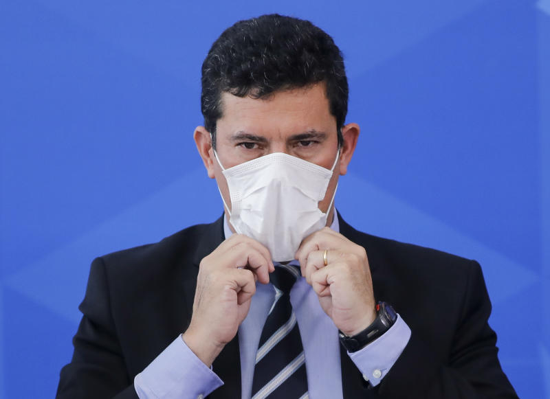 Minister of Justice Sergio Moro covers his face with a face cover during a press conference regarding the COVID-19, coronavirus pandemic at the Planalto Palace, Brasilia on March 18, 2020. (Photo by Sergio LIMA / AFP) (Photo by SERGIO LIMA/AFP via Getty Images)