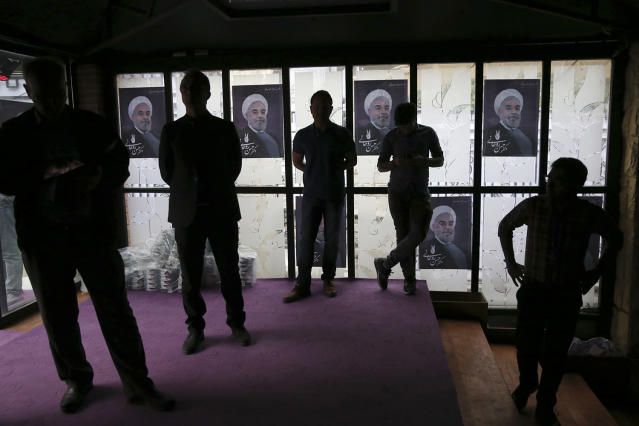 <p>Watchers are silhouetted while following TV debate of Iranian presidential candidates of May 19 elections, in one of electoral campaign offices of President Hassan Rouhani, shown in posters in background, in northern Tehran, Iran, May, 5, 2017. (Photo: Vahid Salemi/AP) </p>