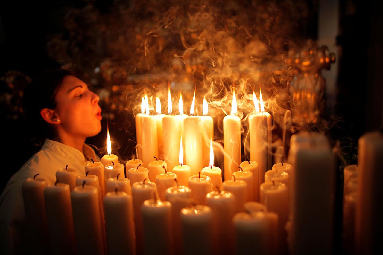 """<p>A penitent of """"Lagrimas y Favores"""" blows out candles inside a church as she takes part in a Palm Sunday procession, marking the start of the Holy Week in Malaga, southern Spain, April 9, 2017. (Photo: Jon Nazca/Reuters) </p>"""