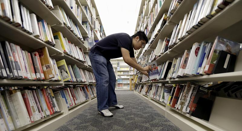 Timothy Ngo shelves books at the Barbara Bush Branch Library Friday, June 28, 2013, in Spring, Texas. The nation's librarians will be recruited to help people get signed up for insurance under President Barack Obama's health care overhaul. Up to 17,000 U.S. libraries will be part of the effort to get information and crucial computer time to the millions of uninsured Americans who need to get coverage under the law. The undertaking will be announced Sunday in Chicago at the annual conference of the American Library Association, according to federal officials who released the information early to The Associated Press. (AP Photo/David J. Phillip)