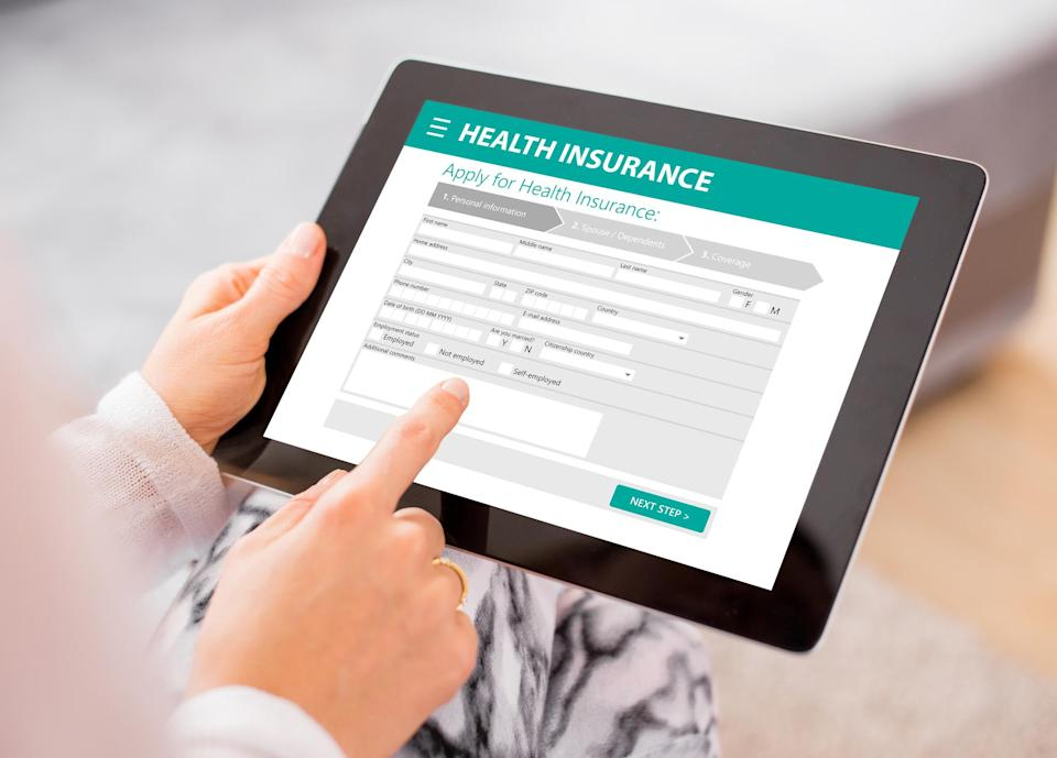 Person filling out a health insurance form on a tablet