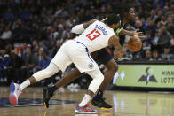 Los Angeles Clippers' Paul George (13) knocks the ball out of the hands of Minnesota Timberwolves' Naz Reid in the first half of an NBA basketball game Saturday, Feb. 8, 2020, in Minneapolis. (AP Photo/Stacy Bengs)