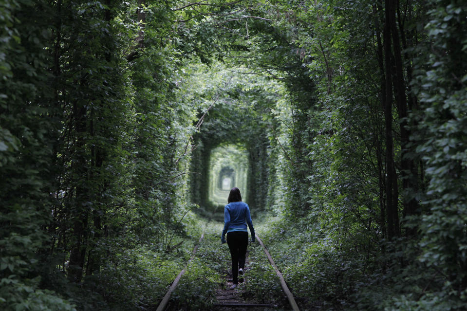 A girl walks on a disused railway line, through what is locally called the