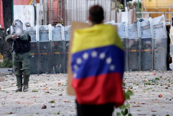 <p>A man with a Venezuelan flag stands in front of riot security forces while rallying against Venezuela's President Nicolas Maduro's government in Caracas, Venezuela, July 26, 2017. (Photo: Ueslei Marcelino/Reuters) </p>