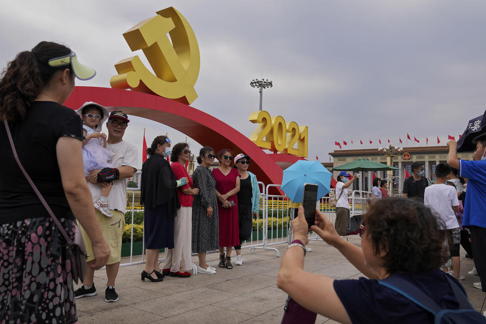 Visitors gather to take souvenir photos with a communist party's logo on display at Tiananmen Square to mark the 100th anniversary of the founding of the ruling Chinese Communist Party in Beijing on Monday, July 5, 2021. Chinese leader Xi Jinping on Tuesday attacked calls from some in the U.S. and its allies to limit their dependency on Chinese suppliers and block the sharing of technologies. (AP Photo/Andy Wong)