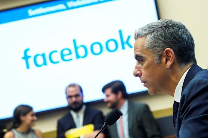 David Marcus, CEO of Facebook's Calibra, is pictured with a microphone in front of a Facebook background.