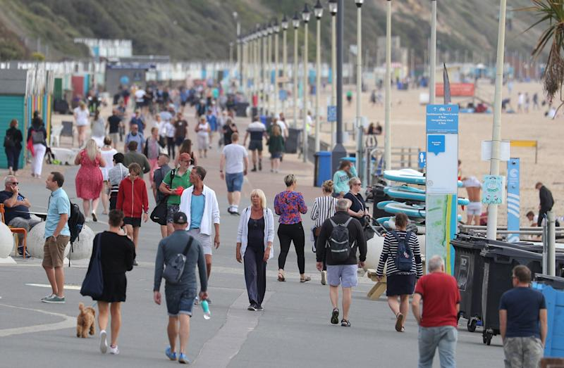 People walk along the beach front at Boscombe beach in DorsetPA