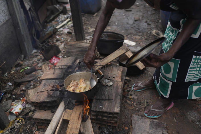 Lady Laurentino, 74, cooks in a wood fire near the door of her home in the Jardim Gramacho favela of Rio de Janeiro, Brazil, Monday, Oct. 4, 2021. With the surge in cooking gas prices, Laurentino says she is cooking with wood because she doesn't have money to buy another cooking gas cylinder. (AP Photo/Silvia Izquierdo)