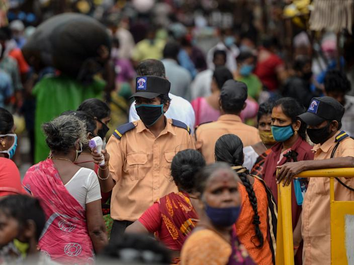 """A security personnel checks the body temperature of a woman as she enters a market in Chennai, India, on July 29, 2020. <p class=""""copyright"""">ARUN SANKAR/AFP via Getty Images</p>"""