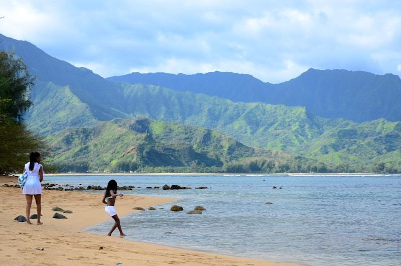 A bather dips a toe into the tempting waters of Hanalei, on the north shore of Kauai, Hawaii.