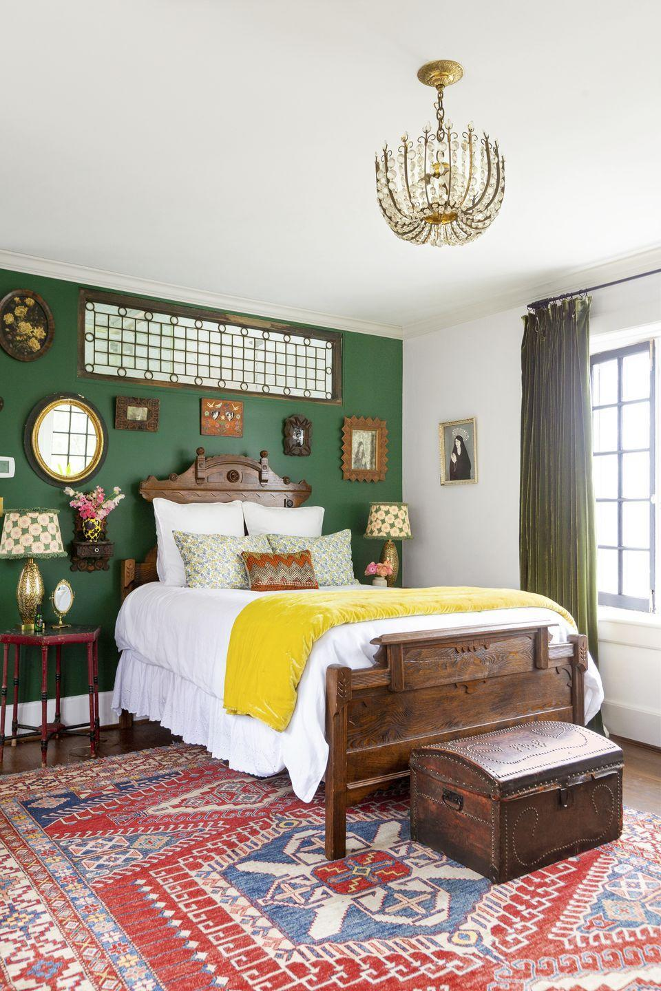"""<p>Don't be afraid to try a strong color, but use it for a single accent wall to provide impact without overwhelming. Here, in homeowner Jen Auerbach's Nashville bedroom, a rich green provides a deep backdrop to a mix of dark wood tones. To add additional light to the room, she installed a 1930s leaded glass window as a pass-through window on the wall separating the bedroom and bath. </p><p><strong>Get the Look: <br></strong>Accent Wall Paint Color: <a href=""""https://www.sherwin-williams.com/homeowners/color/find-and-explore-colors/paint-colors-by-family/SW6454-shamrock"""" rel=""""nofollow noopener"""" target=""""_blank"""" data-ylk=""""slk:Shamrock by Sherwin-Williams"""" class=""""link rapid-noclick-resp"""">Shamrock by Sherwin-Williams</a></p>"""