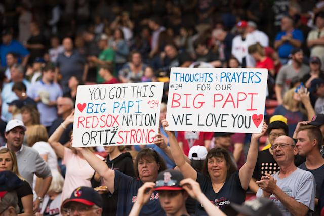 Fans hold up signs showing support for former Red Sox player David Ortiz, who was shot in the back while at a club in the Dominican Republic. (Getty Images)