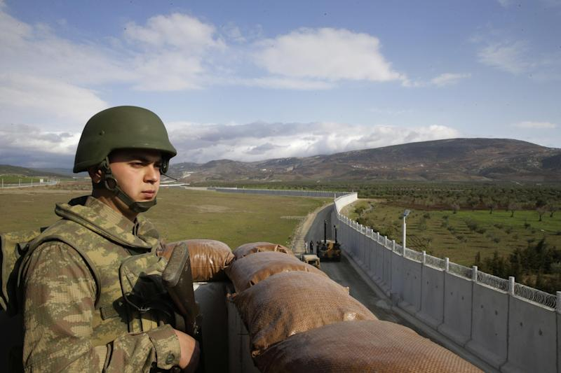 FILE - In this Thursday, March 2, 2017 file photo, a Turkish army soldier mans an outpost near the town of Kilis, southeastern Turkey, adjacent to the wall the country had been constructing to boost security along its border with conflict-stricken Syria. A U.N. humanitarian agency said Sunday, March 5, 2017, that some 66,000 people have been displaced in five months of fighting in Syria's crowded northern battlefield. Turkish, Syrian government, Syrian opposition, and autonomous Kurdish-led forces have all been jostling for territory formerly held by the Islamic State group near the Turkish-Syrian frontier, as preparations are being made to attack the extremists' de facto capital, Raqqa. (AP Photo/Lefteris Pitarakis, File)