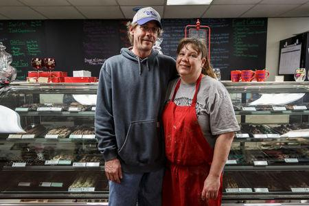 """Travis and Kristy Vliet pose during a momentary break from dipping chocolate strawberries on Valentine's Day in Kristy's """"5 Kidz Kandy"""" store in Waynesburg, Pennsylvania, U.S., February 14, 2018. Picture taken February 14, 2018. REUTERS/Maranie Staab"""