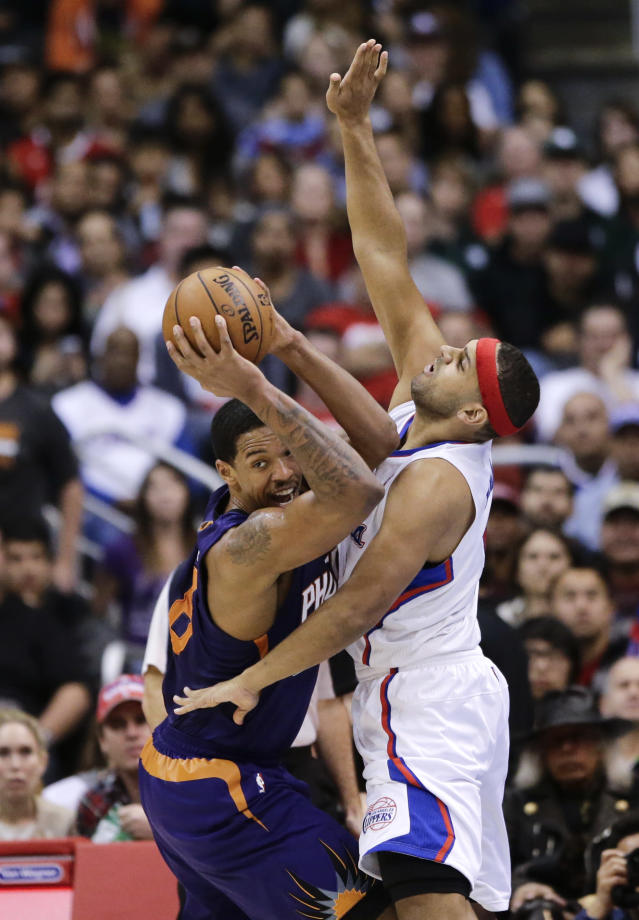 Phoenix Suns' Channing Frye, left, looks to pass as he is defended by Los Angeles Clippers' Jared Dudley during the first half of an NBA basketball game on Monday, Dec. 30, 2013, in Los Angeles. (AP Photo/Jae C. Hong)