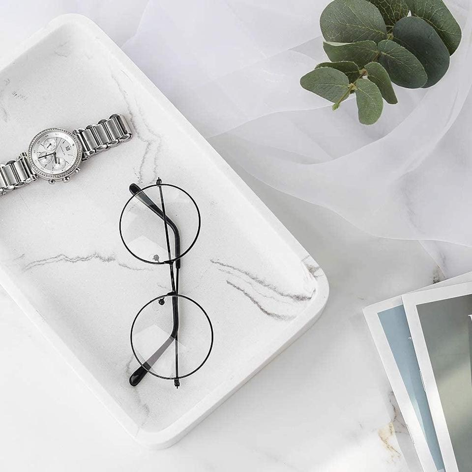 <p>This <span>Luxspire Marble Vanity Decorative Tray</span> ($20) is great for holding all your favorite jewelry pieces.</p>