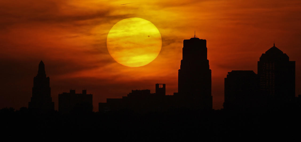 Venus is silhouetted as it crosses in front of the sun as it sets behind the Kansas City, Mo. skyline Tuesday, June 5, 2012. From the U.S. to South Korea, people around the world turned their attention to the daytime sky on Tuesday and early Wednesday in Asia to make sure they caught the once-in-a-lifetime sight of the transit of Venus, which won't be seen for another 105 years. (AP Photo/Charlie Riedel)