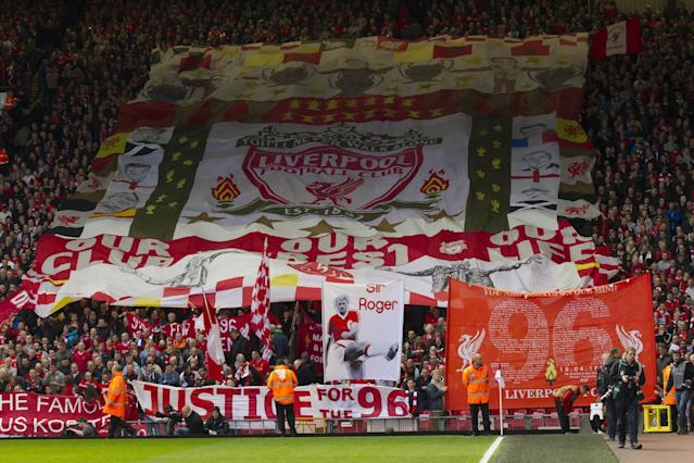 Before their English Premier League soccer match at Anfield Stadium against Manchester City Liverpool supporters hold banners prior to a minute's silence in tribute to the 96 supporters who lost their lives in the Hillsborough disaster of 25 years ago on 15 April 1989, Liverpool, England, Sunday April 13, 2014. (AP Photo/Jon Super)