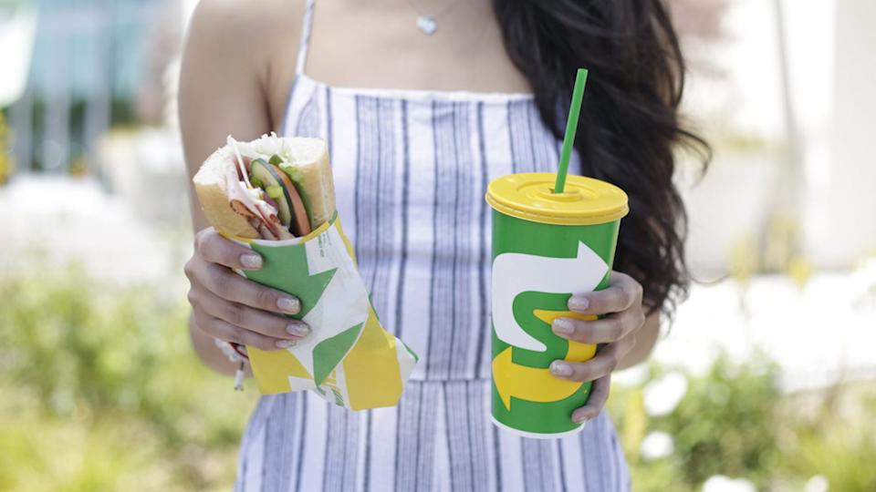 A woman holding a Subway sandwich and a Subway drink.