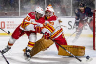 Calgary Flames' Oliver Kylington (58) clears a shot for goaltender David Rittich (33) against the Winnipeg Jets during the second period of an NHL Heritage Classic outdoor hockey game in Regina, Canada, Saturday, Oct. 26, 2019. (Liam Richards/The Canadian Press via AP)