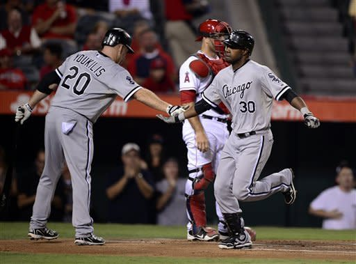 Chicago White Sox's Alejandro De Aza, right, is congratulated by Kevin Youkilis after hitting a solo home run during the first inning of their baseball game, Friday, Sept. 21, 2012, in Anaheim, Calif. Los Angeles Angels catcher Chris Iannetta is at center. (AP Photo/Mark J. Terrill)