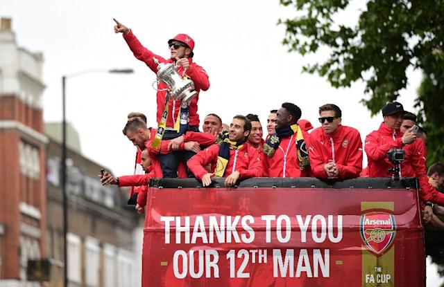 Arsenal's English midfielder Jack Wilshere holds the trophy as he stands with teammates on the top deck of an open-topped bus during the Arsenal victory parade in London on May 31, 2015, following their win in the English FA Cup final (AFP Photo/Leon Neal)