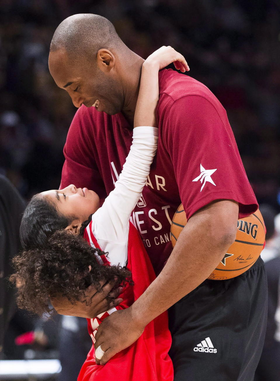 In this Feb. 14, 2016, file photo, Los Angeles Lakers Kobe Bryant (24) hugs his daughter Gianna on the court in warm-ups before first half NBA All-Star Game basketball action in Toronto. Bryant, his 13-year-old daughter, Gianna, and several others are dead after their helicopter went down in Southern California on Sunday, Jan. 26, 2020. (Mark Blinch/The Canadian Press via AP)