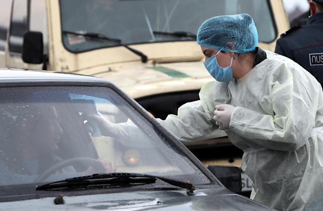 A medical worker is pictured measuring the temperature of a car driver at an entrance to the city of Vagharshapat in Armenia on 16 March. (Getty Images)
