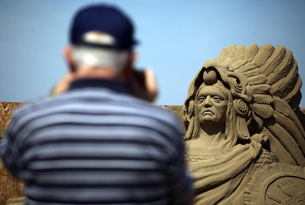WESTON-SUPER-MARE, ENGLAND - JULY 04:   A visitor to Weston-super-Mare's Sand Sculpture Festival stops to take a photograph of some of the sand art on July 4, 2011 in Weston-Super-Mare, England. Now in its fourth year and with a Amazon Jungle theme for 2011, the seaside resort's event attracts top sand sculptors from across the world and runs throughout the summer months.  (Photo by Matt Cardy/Getty Images)