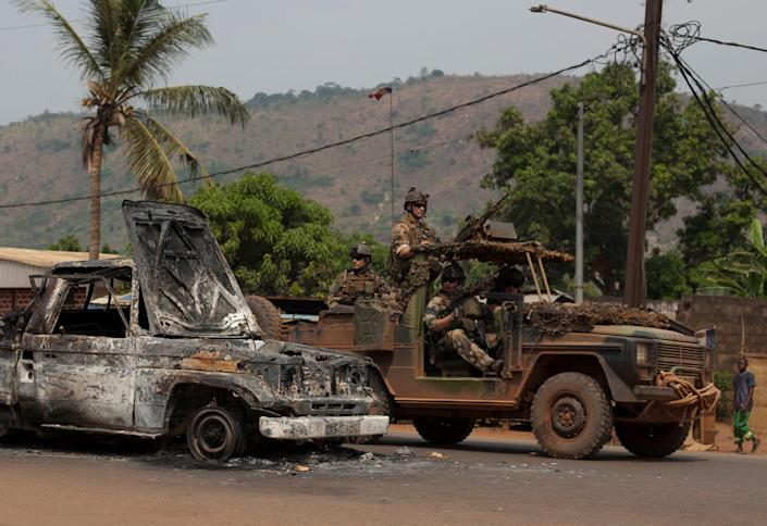 French soldiers drive past the burnt-out shell of a pick-up truck in the Gobongo neighborhood of Bangui, Central African Republic, Thursday, Dec. 26, 2013. Residents and anti-balaka militiamen claimed the neighborhood had been attacked by Chadian soldiers firing rockets, and that anti-balaka militiamen had retaliated by destroying a pick-up truck carrying soldiers with a grenade. Their account could not be independently verified. Several nearby homes and shops were destroyed. The spokesman for an African Union peacekeeping force says six Chadian peacekeepers were killed and 15 were wounded, after being attacked Wednesday. The Chadian contingent, which is made up of Arabic-speaking Muslim soldiers, has been accused of taking sides against the Christian population in the country's sectarian conflict. (AP Photo/Rebecca Blackwell)