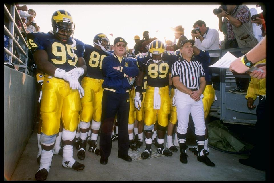 "1 Jan 1990: Head coach Bo Schembechler of the Michigan Wolverines (center) stands with his team during the 1990 Rose Bowl game against the <a class=""link rapid-noclick-resp"" href=""/ncaaw/teams/usc/"" data-ylk=""slk:USC Trojans"">USC Trojans</a> in Pasadena, California. USC won the game 17-10. Mandatory Credit: Mike Powell /Allsport"